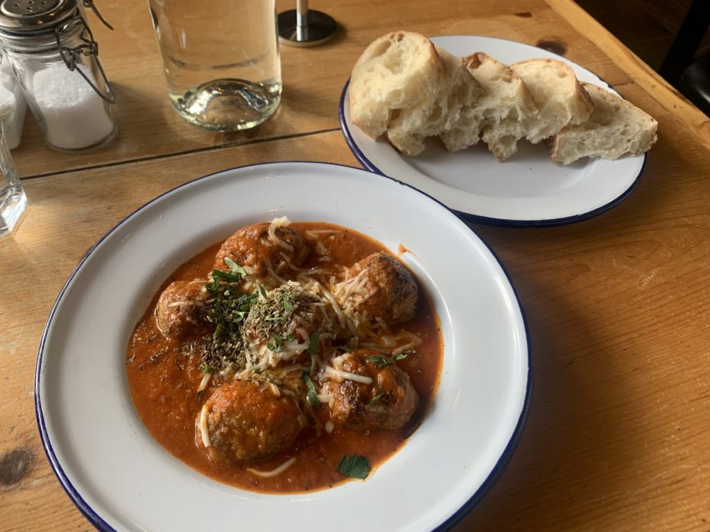 The Keftedes meatballs with kefalotiri cheese, tomato, and slices of bread.