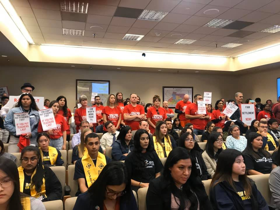 Students and faculty standing and holding signs in protest at the North Orange County Community College District trustee meeting on Feb. 11, 2020.