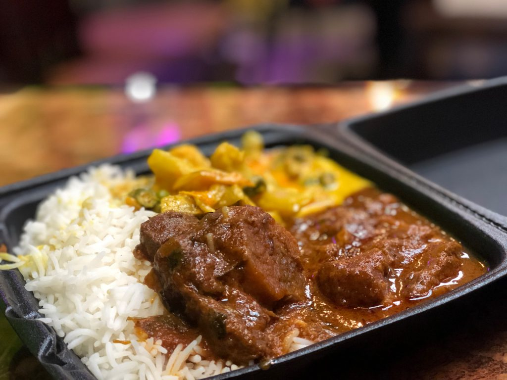 The two-item combo with goat curry  and veggy korma over pouring on a side of basmati rice.
