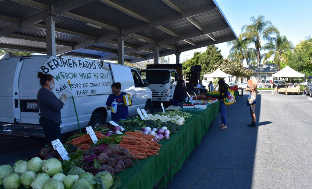 Vendors and customers following guidelines and wearing masks in public at the Fullerton Farmer's Market on the Fullerton Public Library's parking lot.