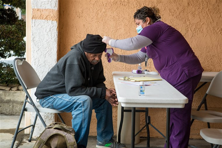 A Registered Nurse takes the temperature of a homeless man as he registers for a hotel room in LA County.
