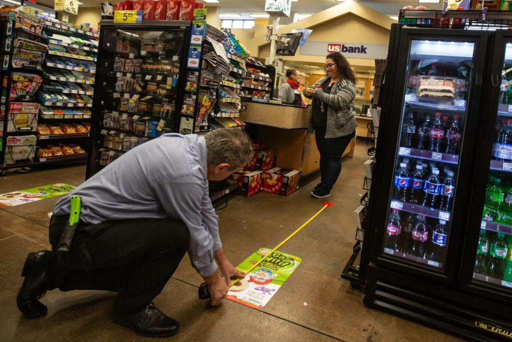 Ralphs employees measure a 6 feet distance for checkout lines.