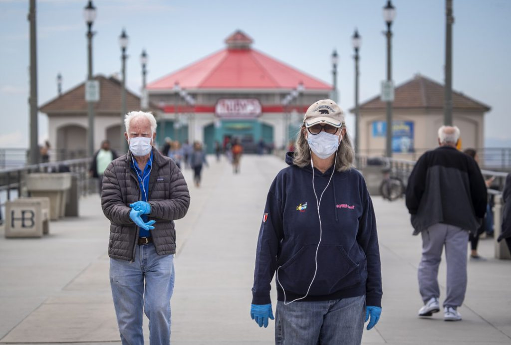 Dallas Weaver, 79, and his wife, Janet Weaver, 75, of Huntington Beach, wear face masks as they finish a walk on the Huntington Beach pier during the coronavirus pandemic.