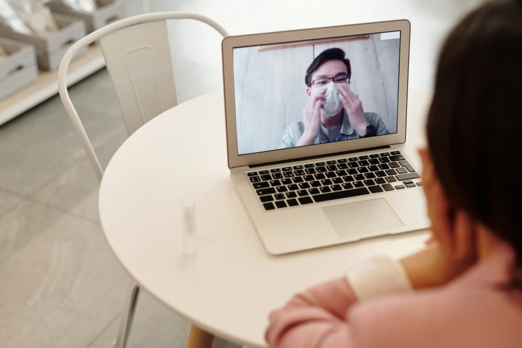 A woman video chats with a man wearing a surgical mask.