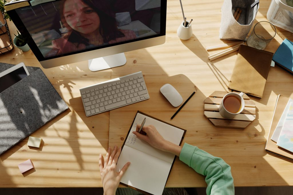 A woman takes notes while video chatting with someone.