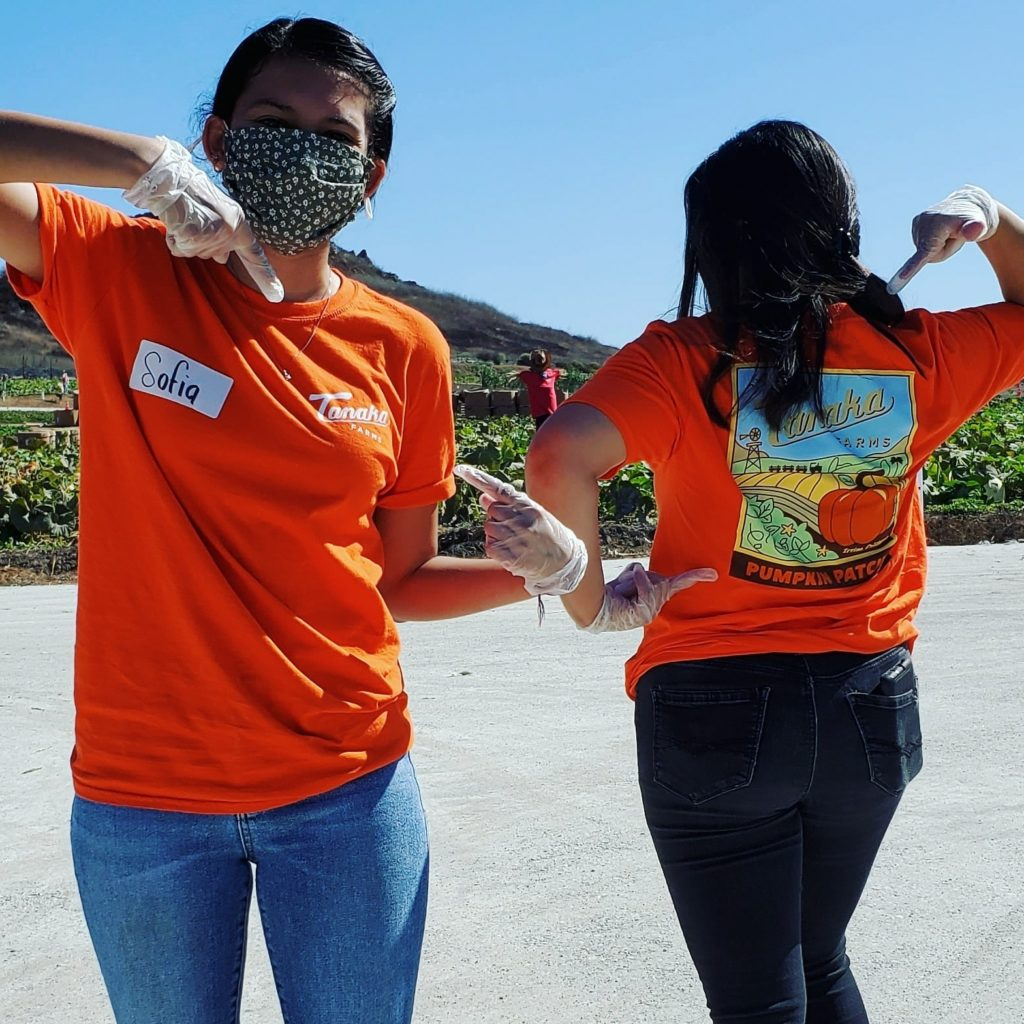 Tanaka Farms employees show off new merchandise while wearing protective gear.