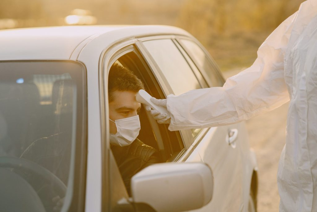 Man gets his temperature checked in his car.