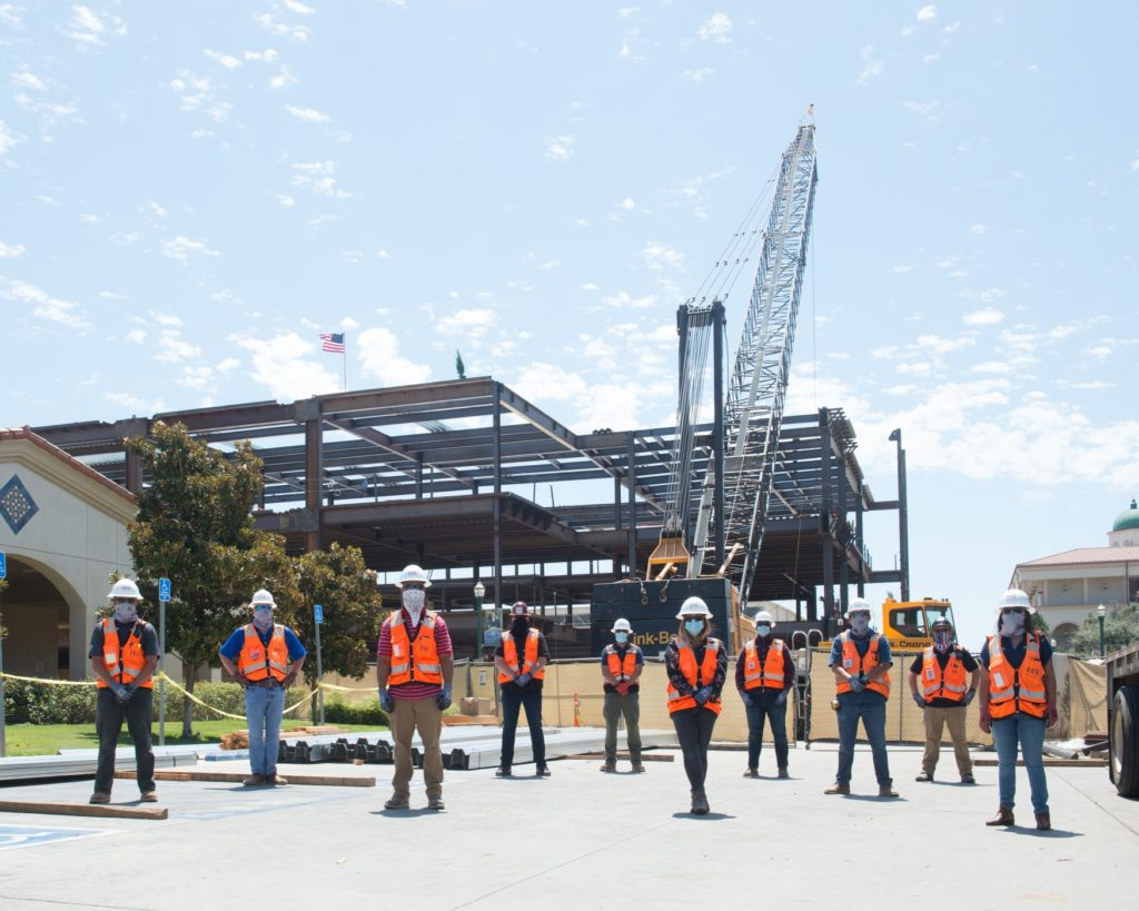 Workers and staff stand in front of the buildings steel skeleton.