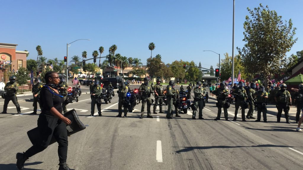 BLM female protestor carrying a shield and walking right by a platoon of OCSD officers.