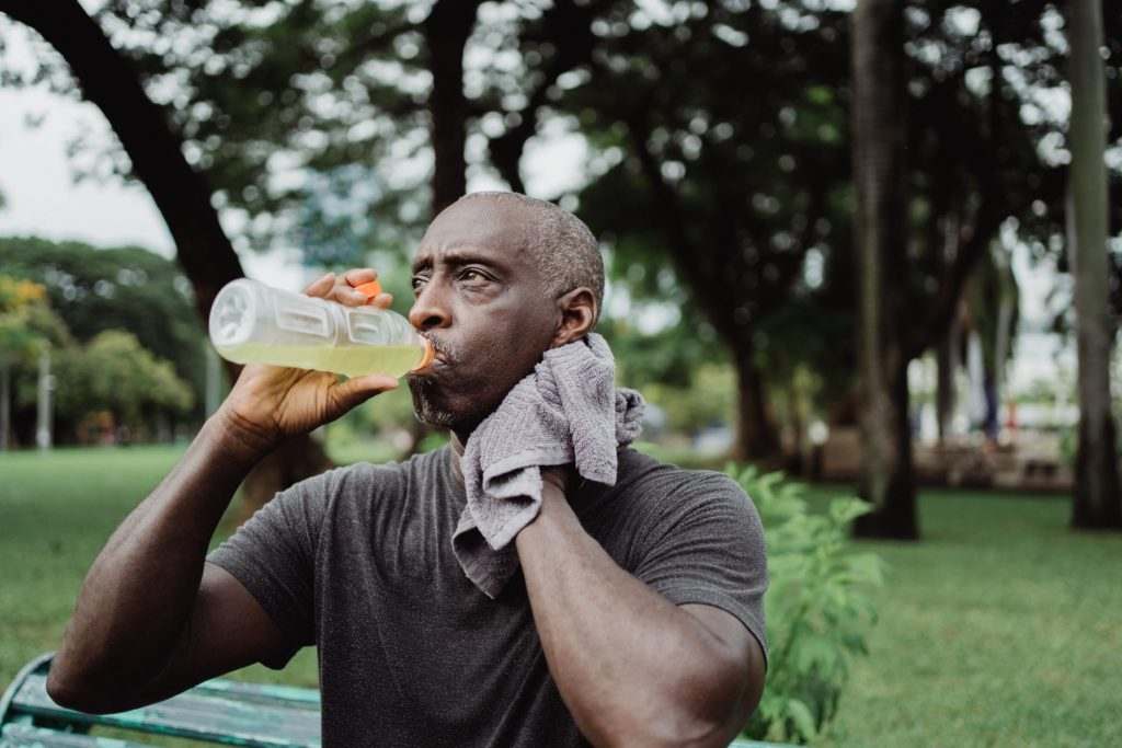 A man drinks a sports drink to stay hydrated.