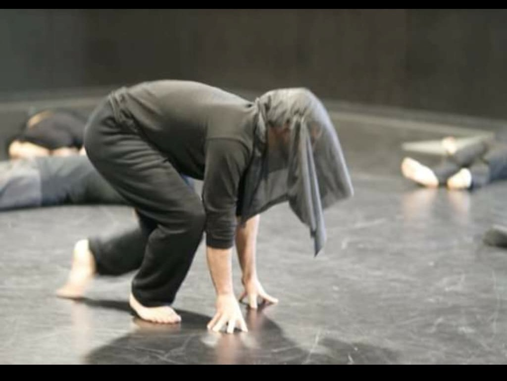 """An actor rises up with their head covered in a black veil, obscuring their identity in a production of """"Ni Una Mas"""" written and directed by Angela Cruz Martinez for the Casa 0101 company in 2010."""