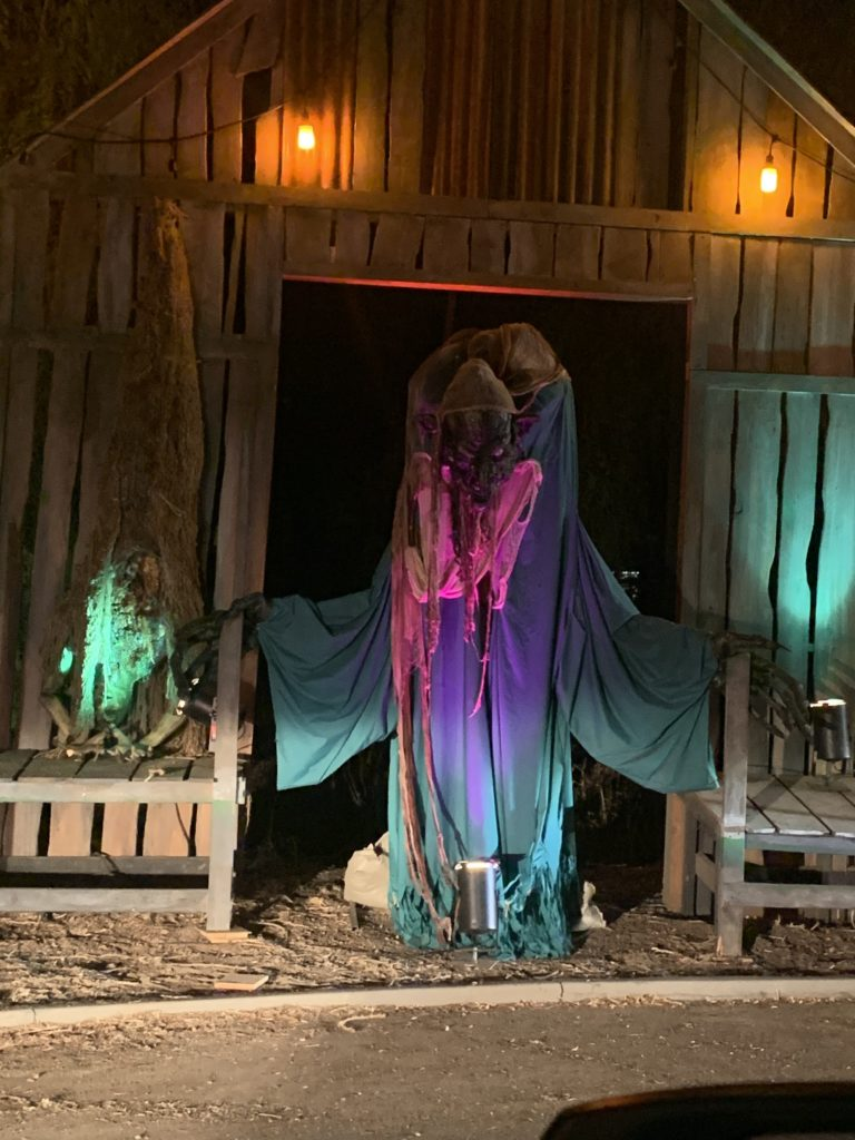 A demon coming out of a raggedy structure in the drive-thru maze of LA Haunted Hayride.