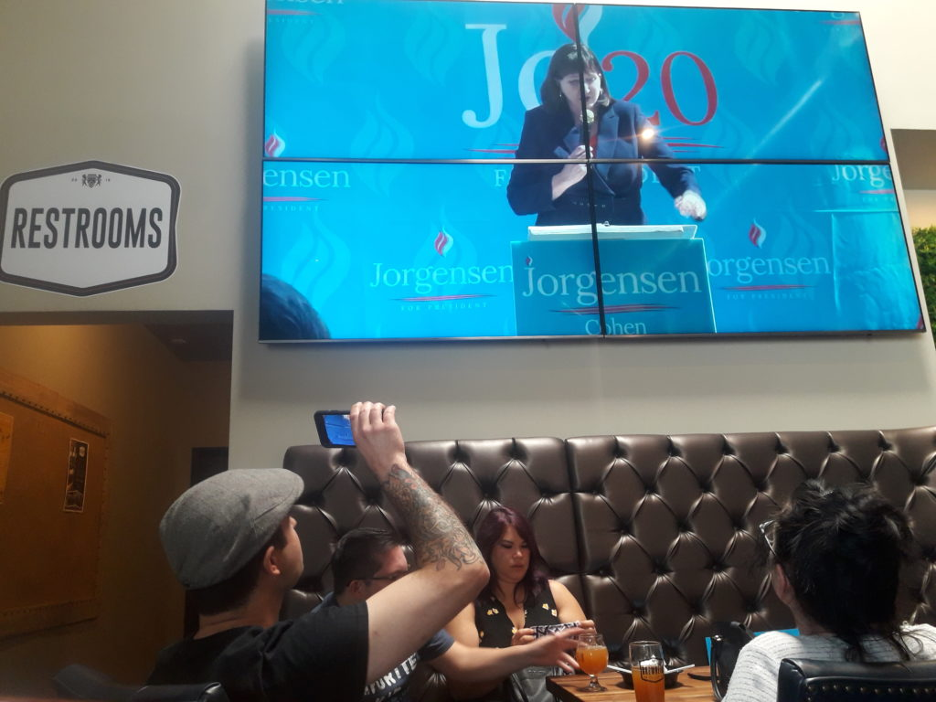 A man records a projection of Jo Jorgensen's live speech in front of the Brewery.