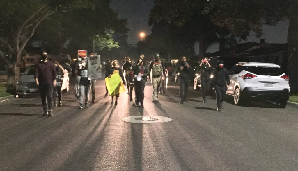 Demonstrators marching down the street in the city of Santa Ana, California.