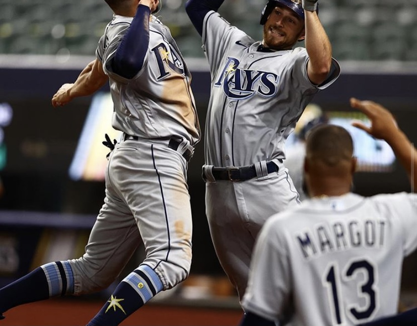 Brandon Lowe (right) celebrates with Willy Adames (left) with Manuel Margot (bottom right)