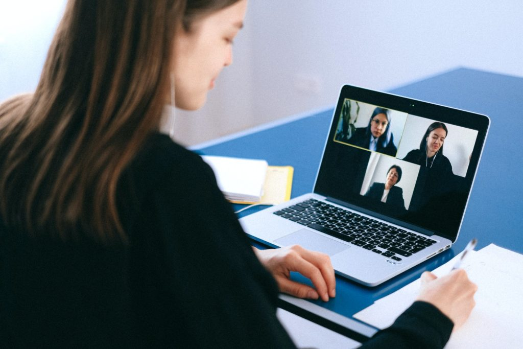 A woman takes notes while attending an online video call.