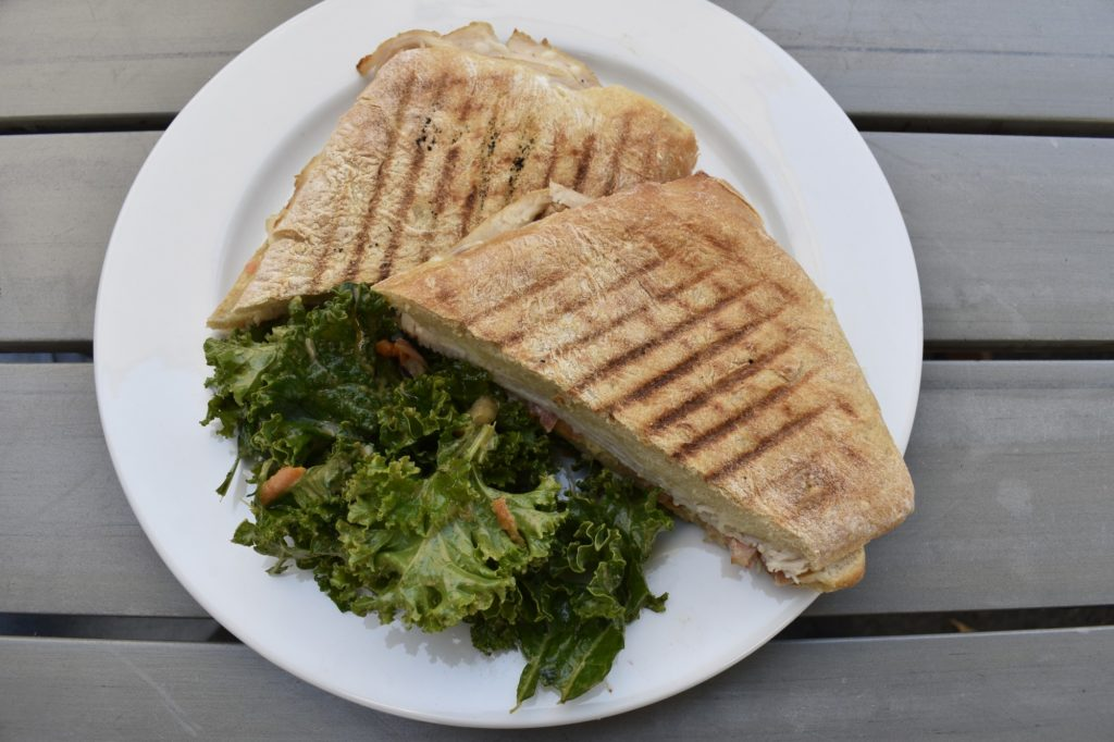The Turkey and Bacon panini is served with a small side of the Green Bliss salad. The panini contains turkey, bacon, cheese, tomato and Dijon mayonnaise.