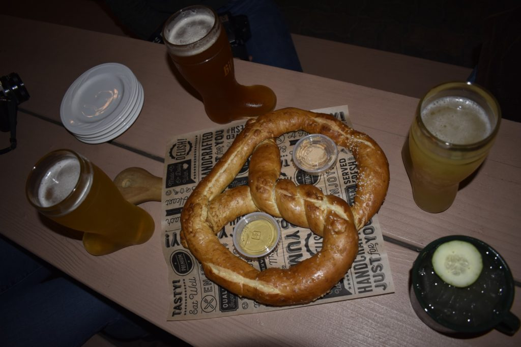Large pretzel served at Old World Oktoberfest with a side of mustard and horseradish. Also pictured are beers and a cocktail.
