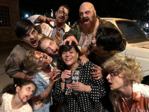 A group of performers in their zombie makeup and costumes surround an audience member after the 2018 production of Night of the Living Dead.