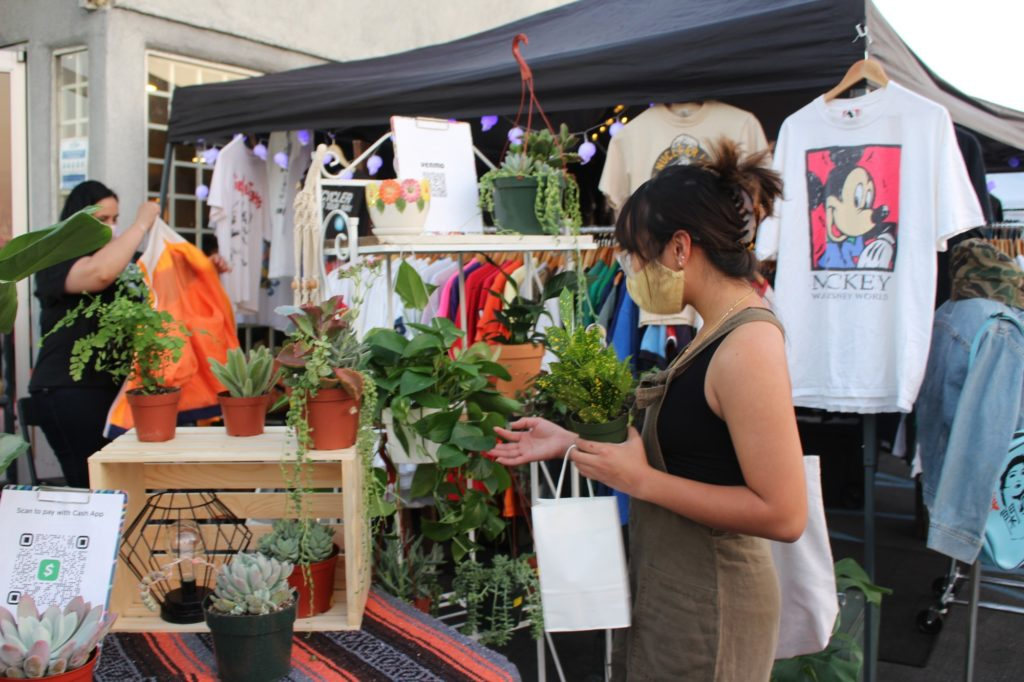 A guest is drawn toward plants displayed in front of a rack of vintage-inspired t-shirts.