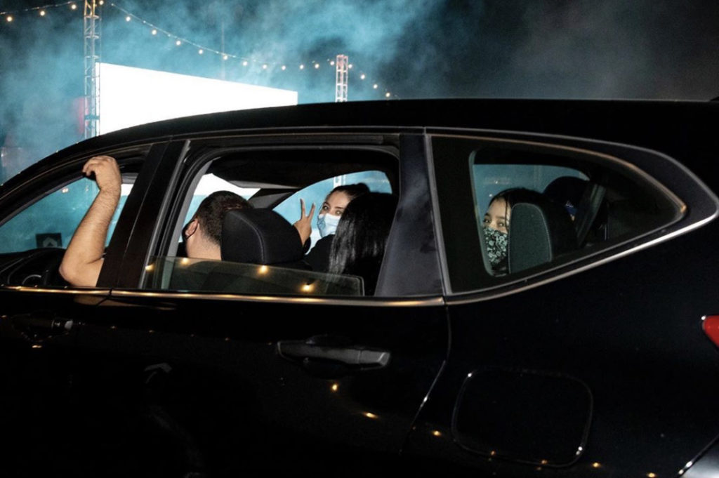 Visitors wearing their masks in their parked cars watching the introduction in the first scene of the event.