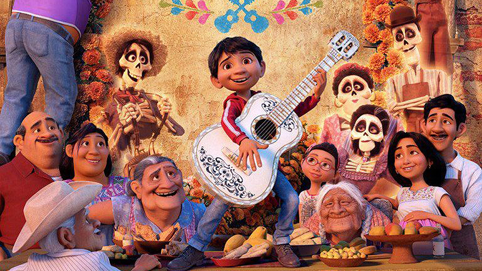 Coco playing the guitar in front of his family while celebrating Día De Los Muertos, a famous traditional holiday that is celebrated within the Latinx community.