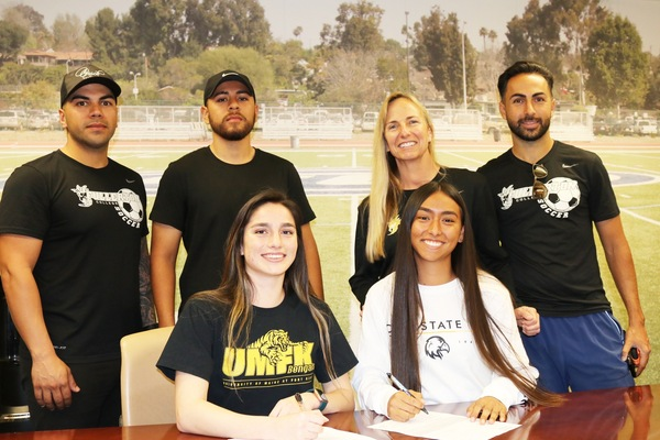 Audrey Ochoa and Kaelah Basurto pictured in February signing with four-year colleges.