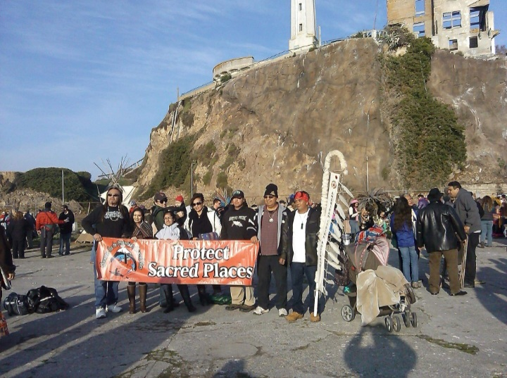 Demonstrators showing a sign from the sunrise ceremony on Alcatraz Island.