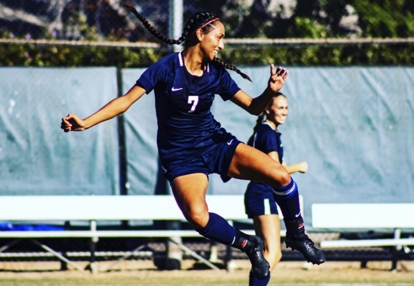Fullerton College woman's soccer players Jumping up to make a kick
