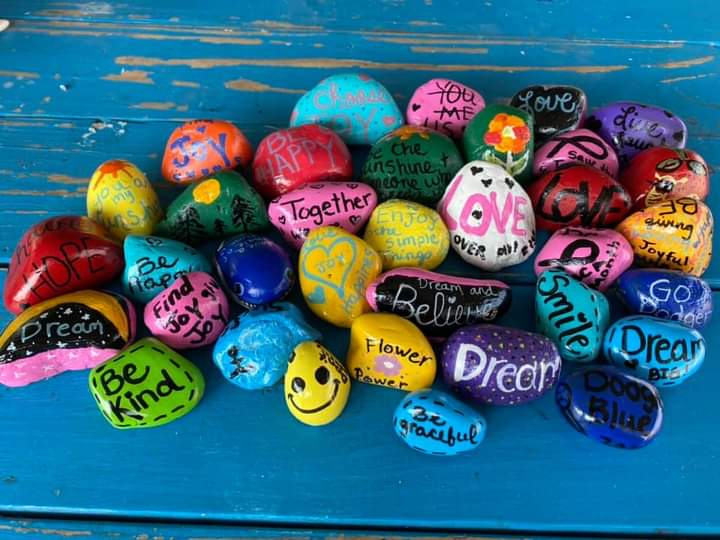 An array of painted rocks with positive messages.
