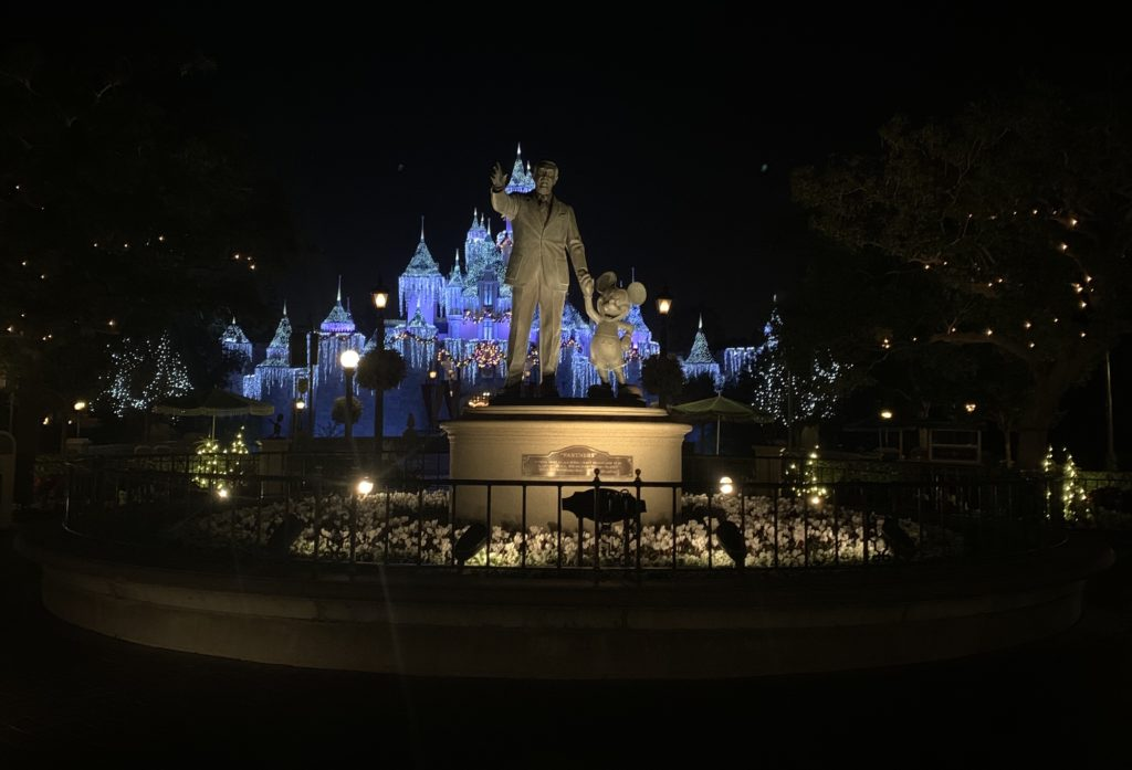 The Disneyland castle with the 2019 holiday overlay glistening in the back of the infamous Walt Disney and Mickey statue.