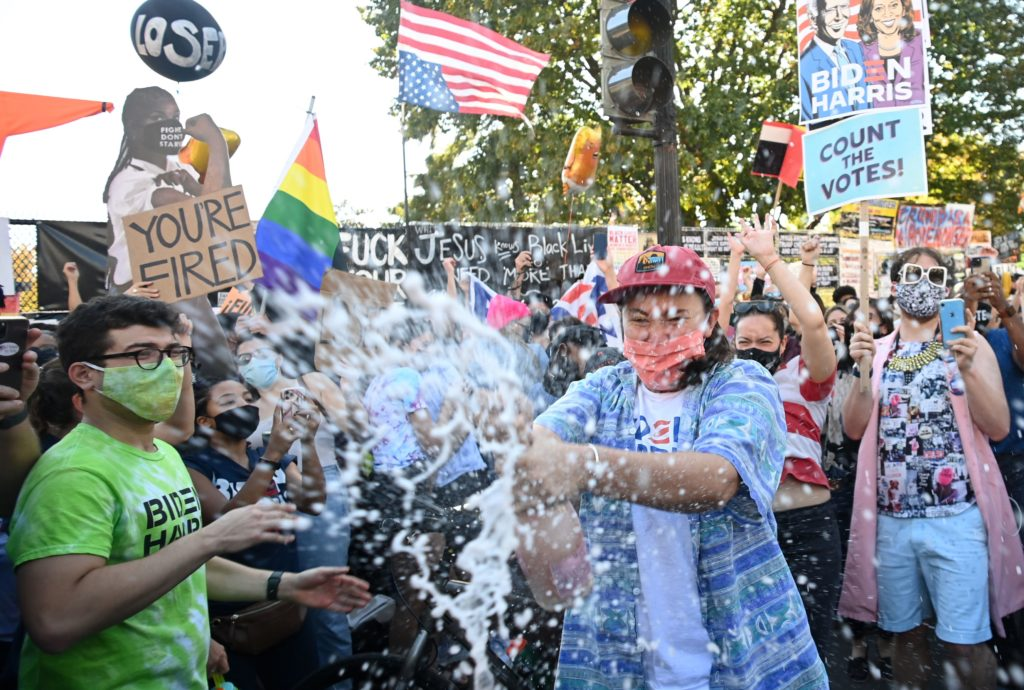A woman sprays prosecco onto the crowd as people celebrate on Black Lives Matter plaza after Joe Biden was declared the winner of the 2020 presidential election.