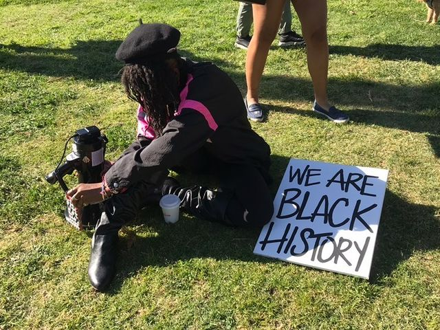 Black activist capturing a photo of an organizer of the Black History Month march.