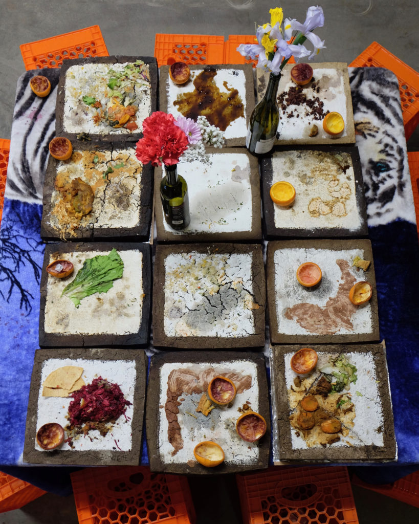 """The remains of an intimate gathering where twelve people ate with their hands from plates made from soil makes Jackie Amézquita&squot;s piece, """"Gathering Number Two""""."""