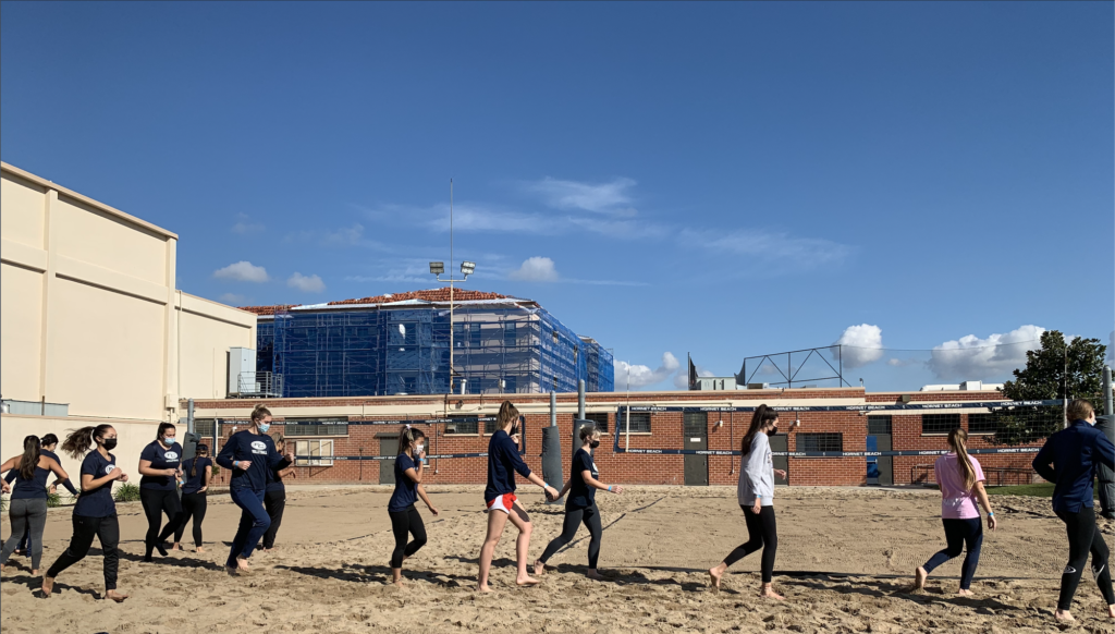 Here the team is seen warming up by jogging around the volleyball court.