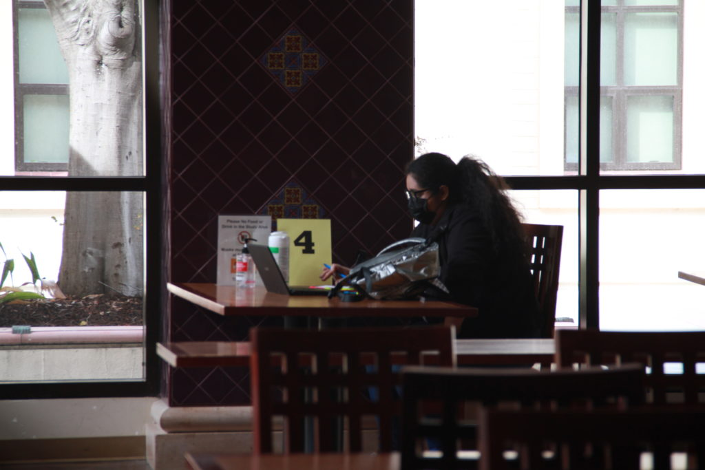 Fullerton College student Leslie Martinez studying on-campus in dining hall.