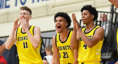 Hornet basketball players Luka Gelb (11), Devin Howlin (21) and Ryen Perry (4) supporting their teammates from the sidelines during the 2019-20 season.
