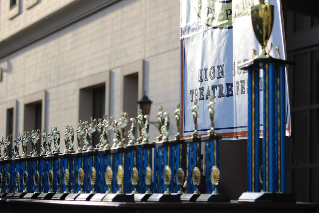 Trophies are lined up for high school students as they compete to win in events such as musical theatre, ensemble acts, monologues, tech olympics and various design categories.