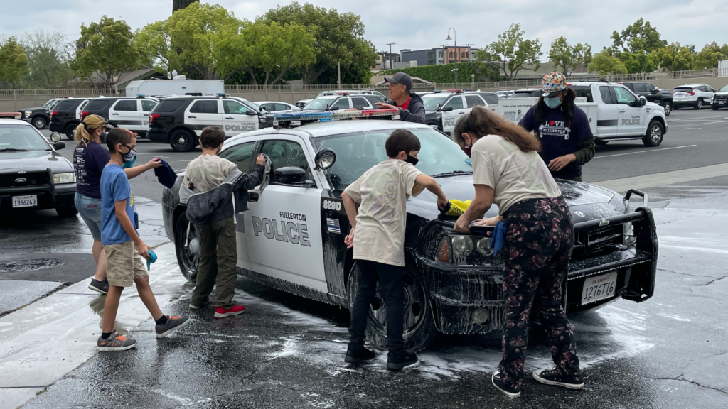 Volunteers, including members of Fullerton's Boy Scout Troop 93 participate in Love Fullerton festivities, battling grime and washing 17 Fullerton PD SUVs, cruisers and an all-terrain vehicle.