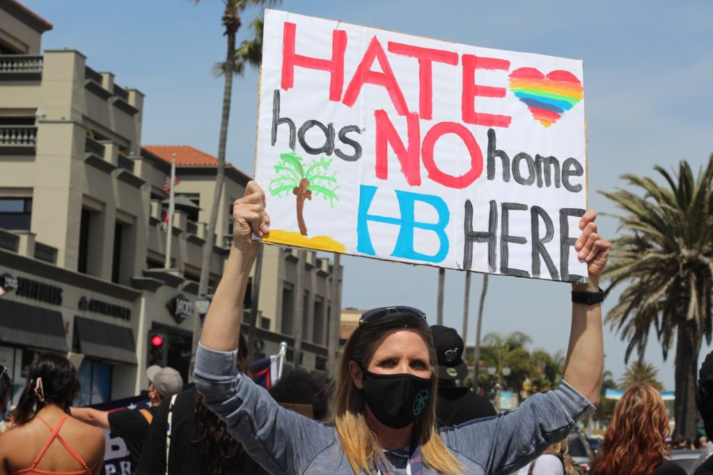 """A Black Lives Matter supporter holding up a sign that reads """"HATE has NO home HERE,"""" with a Huntington Beach symbol. Many Huntington Beach locals were present at the rally in support of Black Lives Matter."""