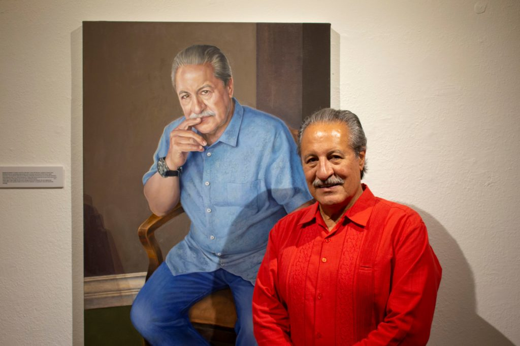 The sponsor for the event and CEO of Alta Med, Cástulo de la Rocha, stands next to his painted portrait