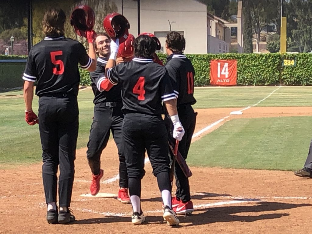 Santa Ana Dons outfielder Micah Pietila-Wiggs celebrates with teammates after hitting a three run home run