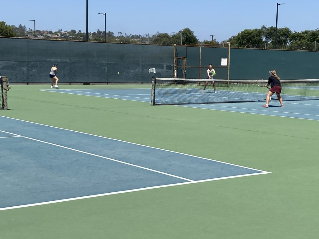 Ashley Castro is in mid-swing during her doubles match with partner Haena So.