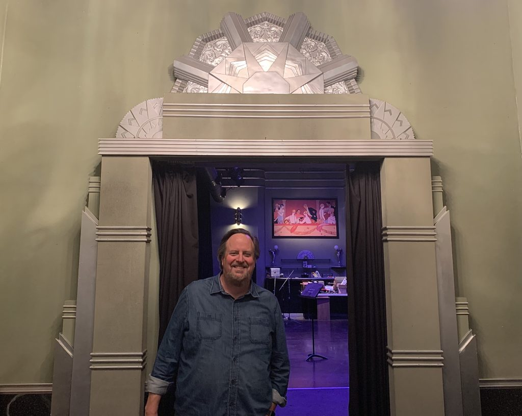 Brian Newell poses for a photo op in front of the theater entrance to the main room.
