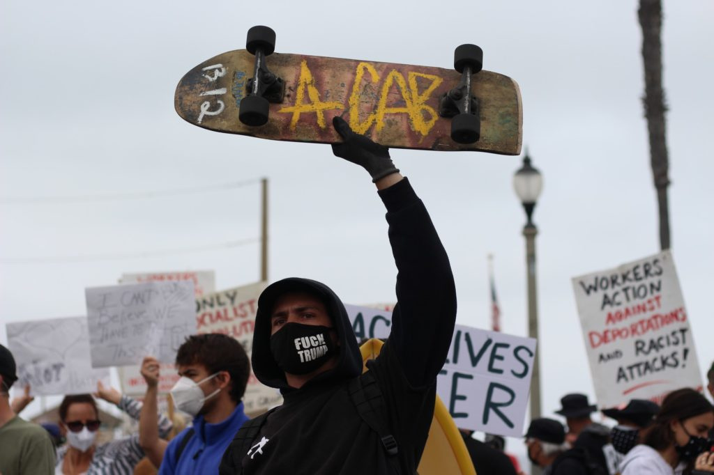 """A protestor holding up his skateboard with """"ACAB"""" written on it. Many Black Lives Matter supporters gathered with signs."""