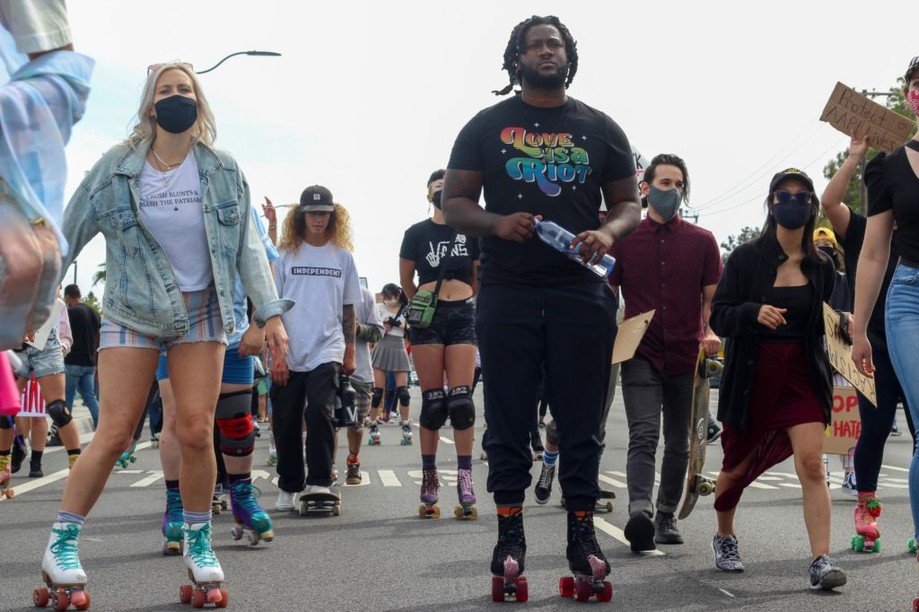 "A diverse group of protestors participated in the Saturday's ""Skate to End Hate"" event. The crowd was a mix of skaters, bikers and pedestrians."