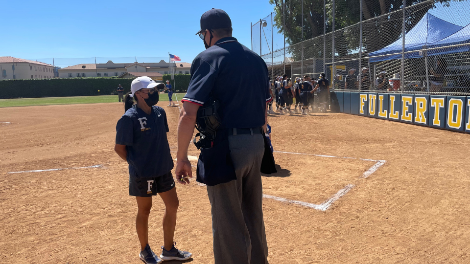 Fullerton College Coach and alumna, Jillian Saiza talks to an Umpire during one of the back to back games played Friday April 30.