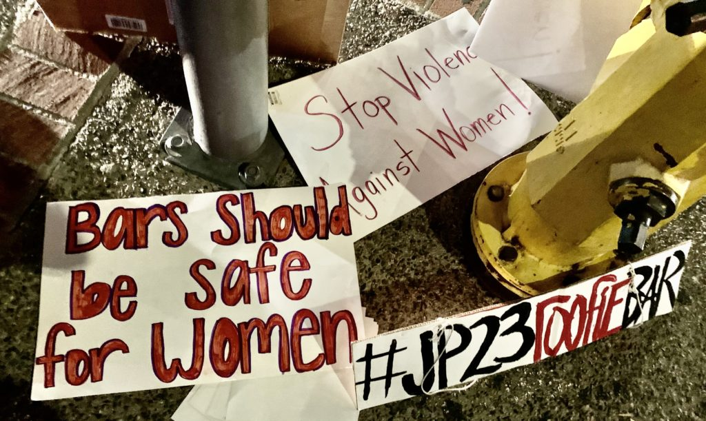 Protester's signs lay on the sidewalk as they chant phrases to discourage people from entering the bar and advocate for the permanent closure of JP23, restaurant and bar.