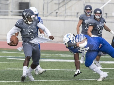 Hornets freshman quarterback Tra Edwards tries to avoid a tackle. Photo Credit: Jim McCormack