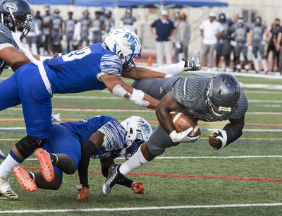 Hornets sophomore running back Branden Rankins is tackled as he protects the ball.  Photo Credit: Jim McCormack